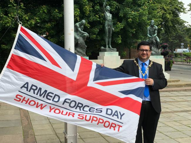 Cllr Asif Khan holds the armed forces day flag outside Watford town hall