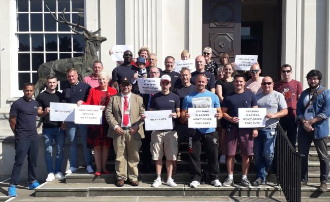Firefighters joined Labour councillors including Cllr Asif Khan and Cllr Nigel Bell on the county hall steps