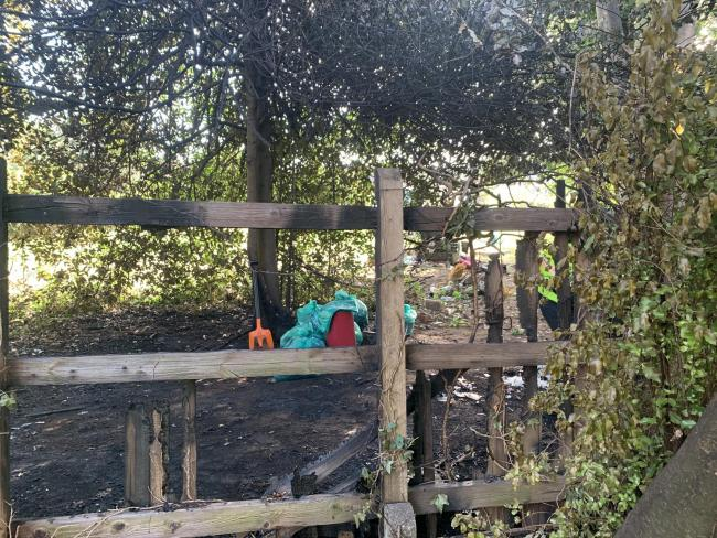 The fence affected by the fire can be seen in front of bagged rubbish