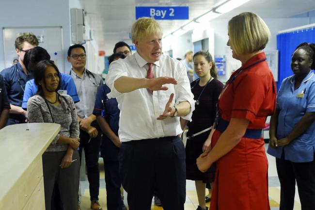 Prime Minister Boris Johnson speaks to medical staff during his visit to Watford General Hospital, following recent announcements on new funding for the NHS. Photo credit: Peter Summers/PA Wire