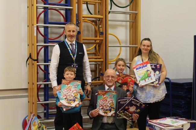 David collects over 360 calendars from the school, accompanied by Riley, 6, and Keira, 7. Credit: West Herts Hospital Trust.