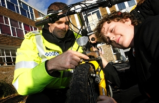 Sergeant Ian Smith and Francis Combe Academy pupil Ben Townsend, 13, perform a bike safety check.