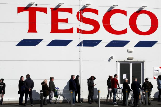 Watford Observer: People queue outside a Tesco Extra store in Madeley, Shropshire