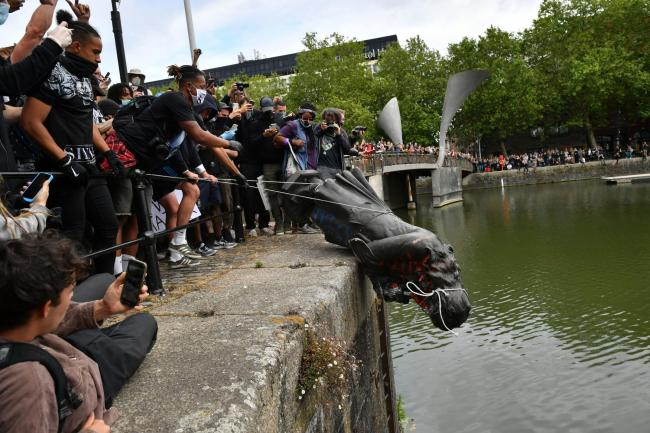 Protesters threw a statue of Edward Colston into Bristol harbour during a Black Lives Matter protest rally. Photo: Ben Birchall/PA Wire