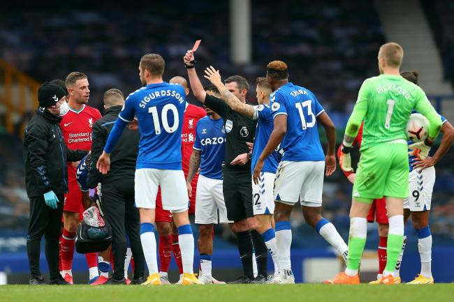 Richarlison, obscured, is shown a red card during the closing stages