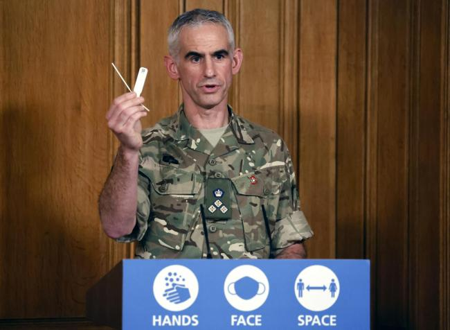British Army Brigadier Joe Fossey, who is coordinating the mass coronavirus testing pilot in Liverpool, holds up the components of a lateral flow Covid-19 test as he speaks during a media briefing in Downing Street on coronavirus. Credit: PA