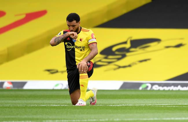 Watford striker Troy Deeney, pictured taking a knee for the Black Lives Matter movement, has revealed the extent of racial abuse he and his family face on social media. Photo: Action Images