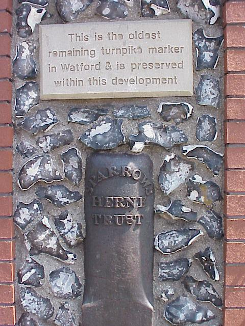 The turnpike marker is embedded in the wall near Bushey Arches