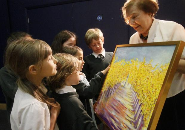 Radlett Art Society Chairman, Carmen Beal, shows youngsters from Fair Field Junior School art work