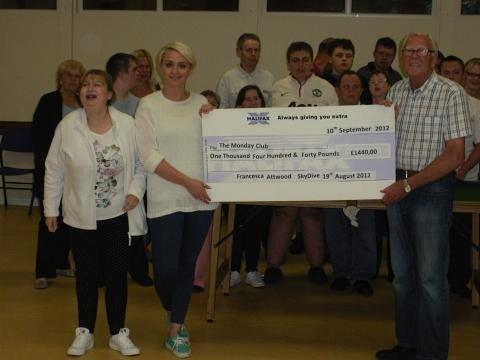 Francesca Attwood presents her massive cheque - in every way - to the delighted Monday Club.