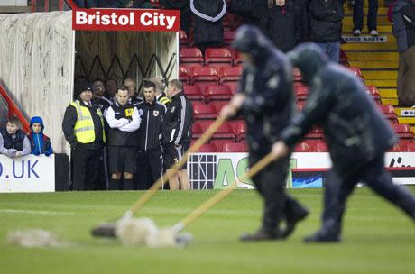 Referee Michael Naylor looks on as Bristol City groundstaff try to clear the pitch of water. Picture: Action Images