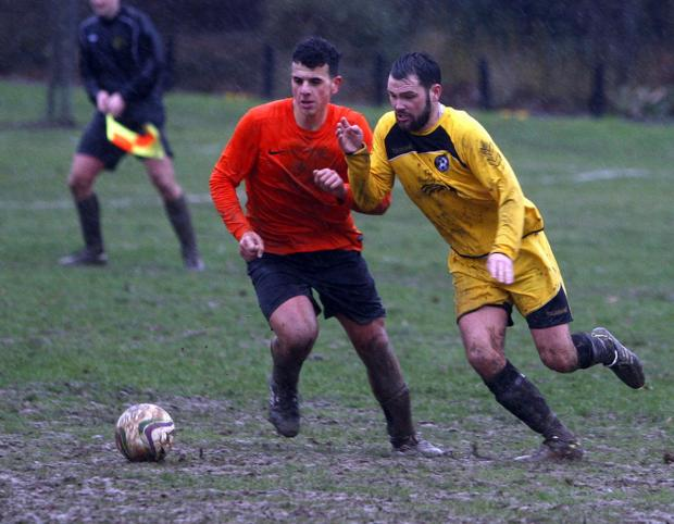 Hertfordshire Lions (orange shirts) battled through the mud but were well beaten by Shenley Wood in the fifth round of the Herts Sunday Junior Cup. Picture: Holly Cant