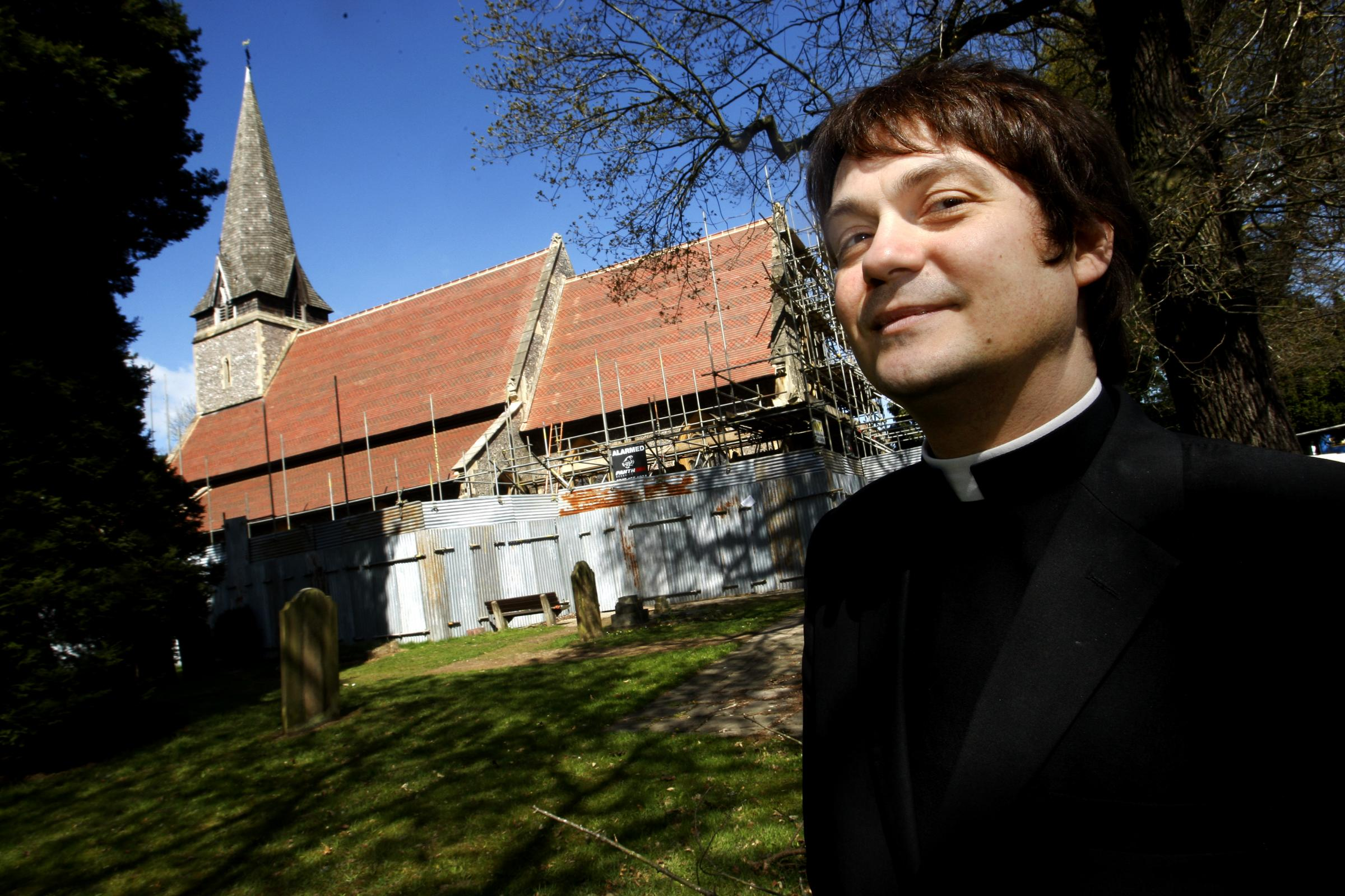 Father Eddie Green outside All Saints Church, Leavesden where new roof is being built