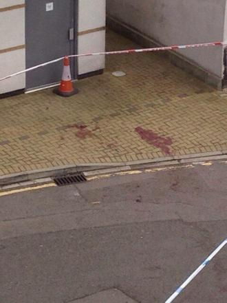 Blood stained pavement cordoned off as police investigate reports of stabbing
