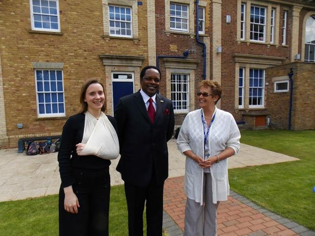 Mr Williams Nkurunziza, the High Commissioner of Rwanda, in Lady's Close gardens with Deputy Head Julie Richards, and Head of English Laura Sutherland (with sling).