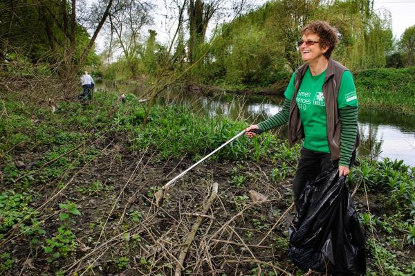 A volunteer helping to keep Oxhey Park tidy