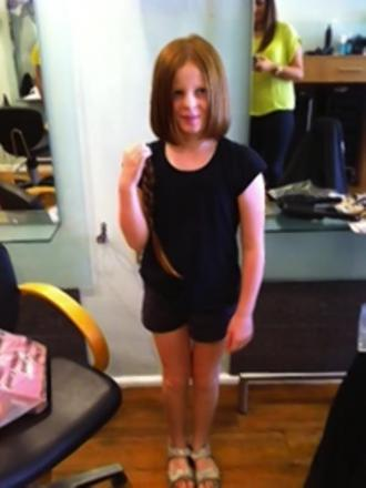 Nine year-old girl has waist-long hair cut off for charity