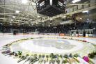 Flowers lie on the ice as people gather for a vigil at the Elgar Petersen Arena (Jonathan Hayward/The Canadian Press via AP)