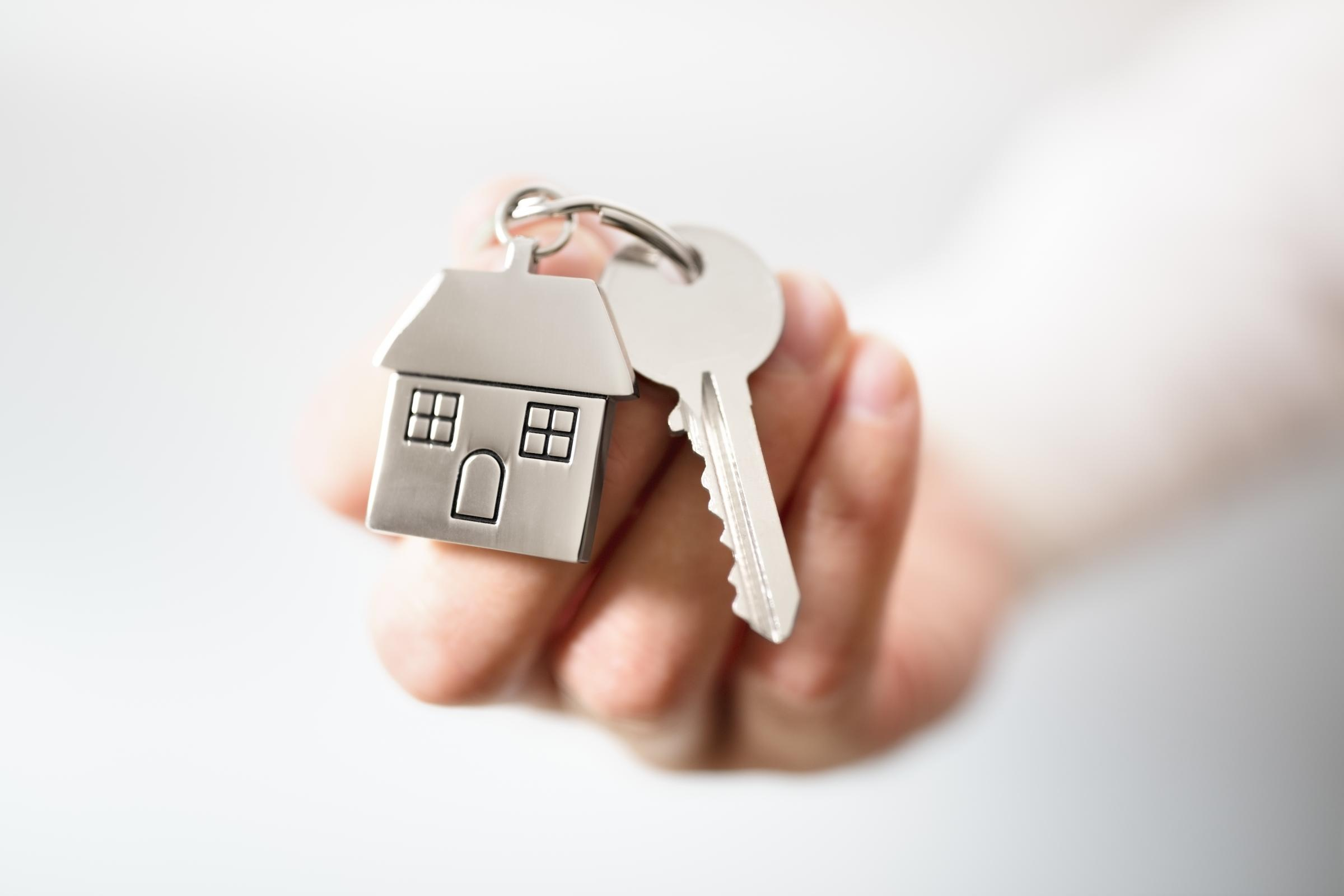 Holding house keys on house shaped keychain concept for buying a new home.