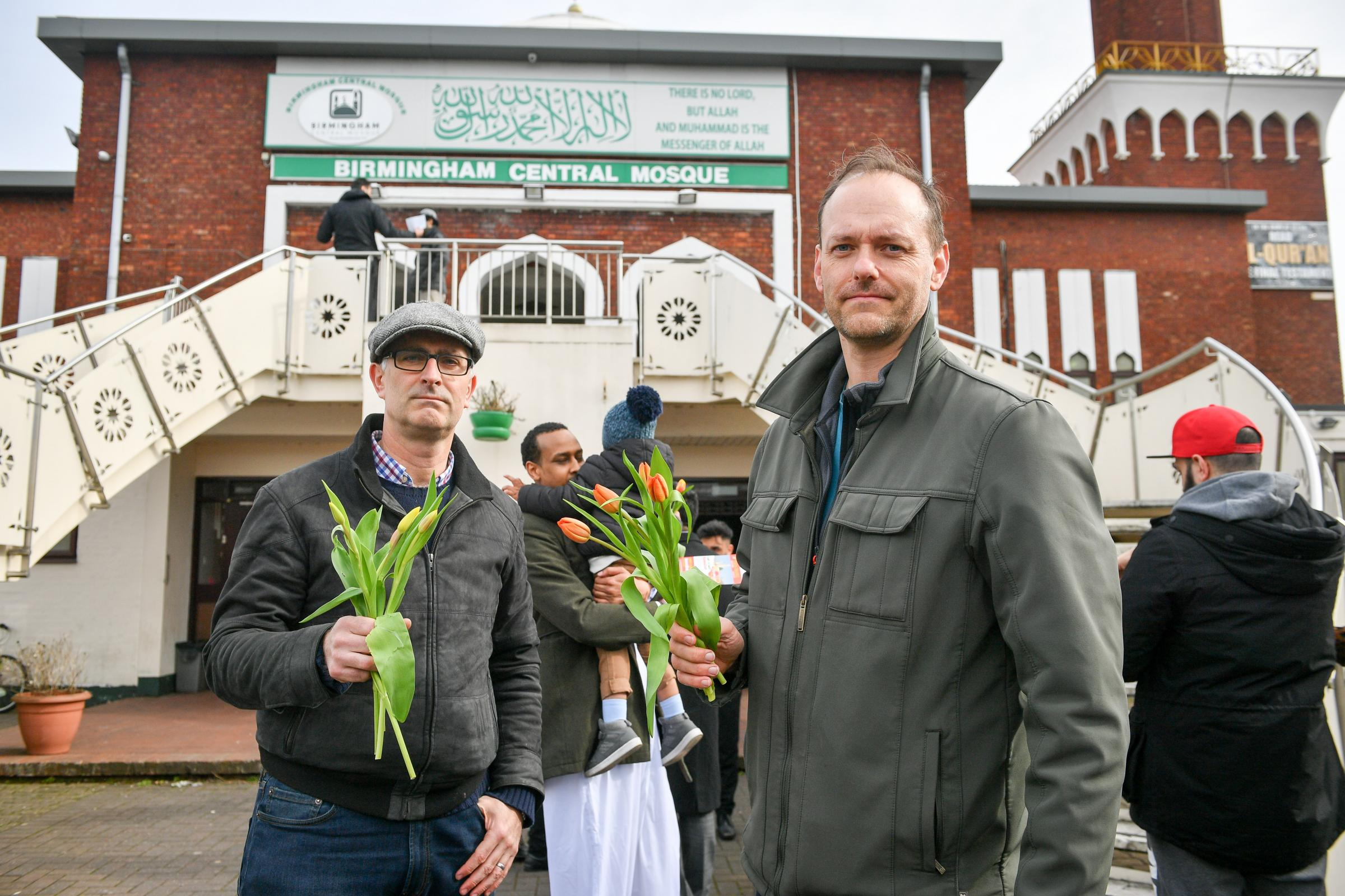 Christians James Lynch, left, and Marcus Kapers from Riverside Church, who are handing out flowers to Muslims as they leave Birmingham Central Mosque after the attack on the Mosque in Christchurch, New Zealand.
