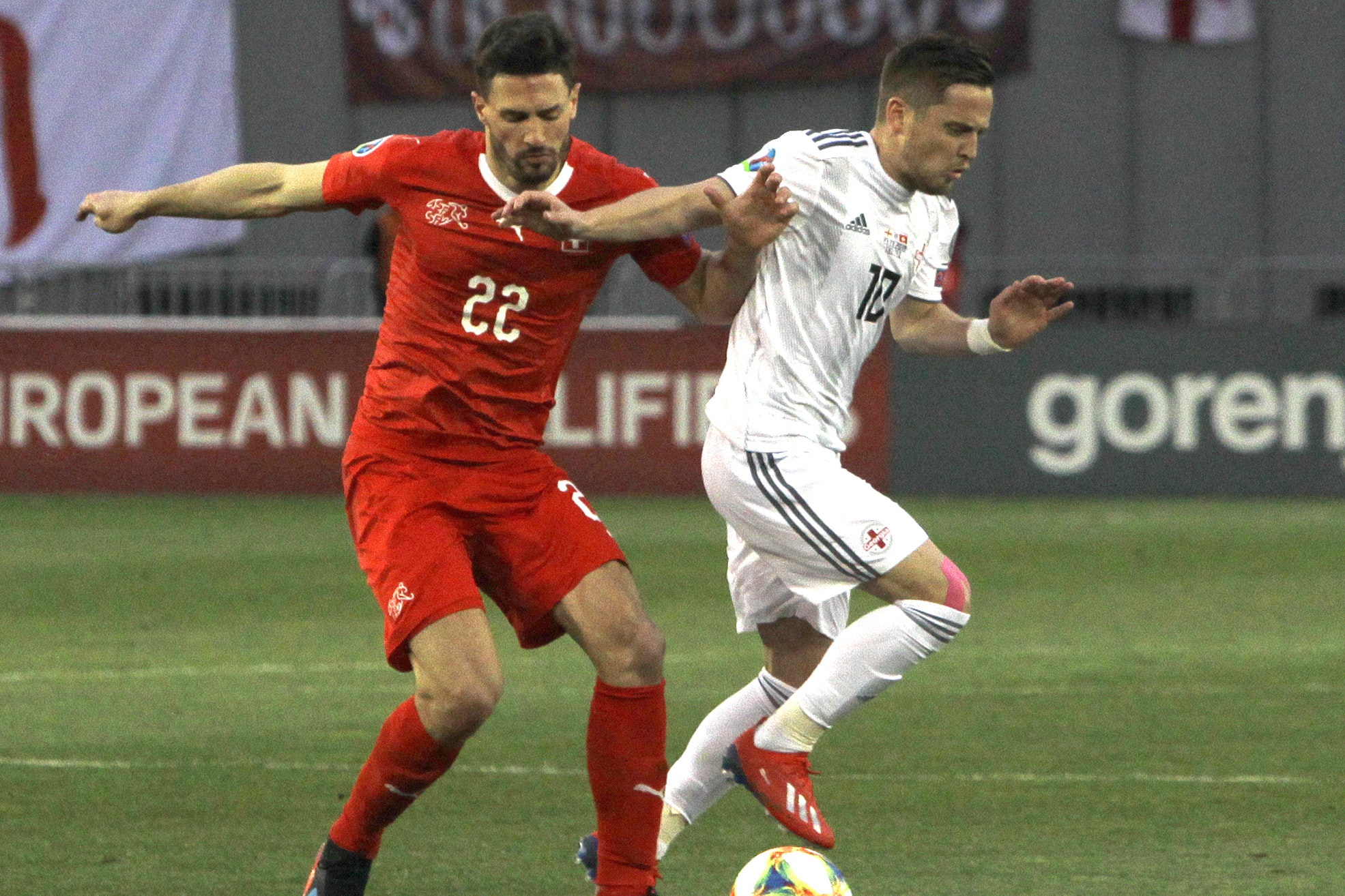 Switzerland's Fabian Schar, left, and Georgia's Jano Ananidze, who is understood to have helped Schar recover after he was knocked ou