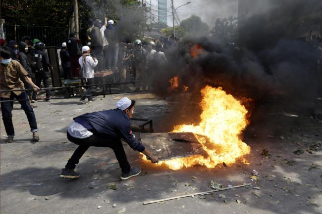 Protesters try to put out fire from a burning tyre in Jakarta